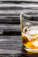 glass of whiskey on dark wooden background